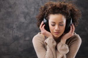 Lady listening to a vinyl record through headphones