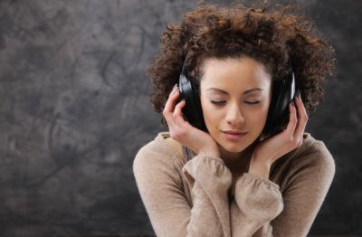 Lady listening to record player using headphones
