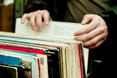 Hands picking through a collection of vinyl records