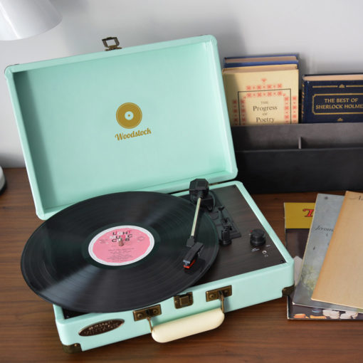 mBeat Woodstock record player tiffany blue shown on desk with books