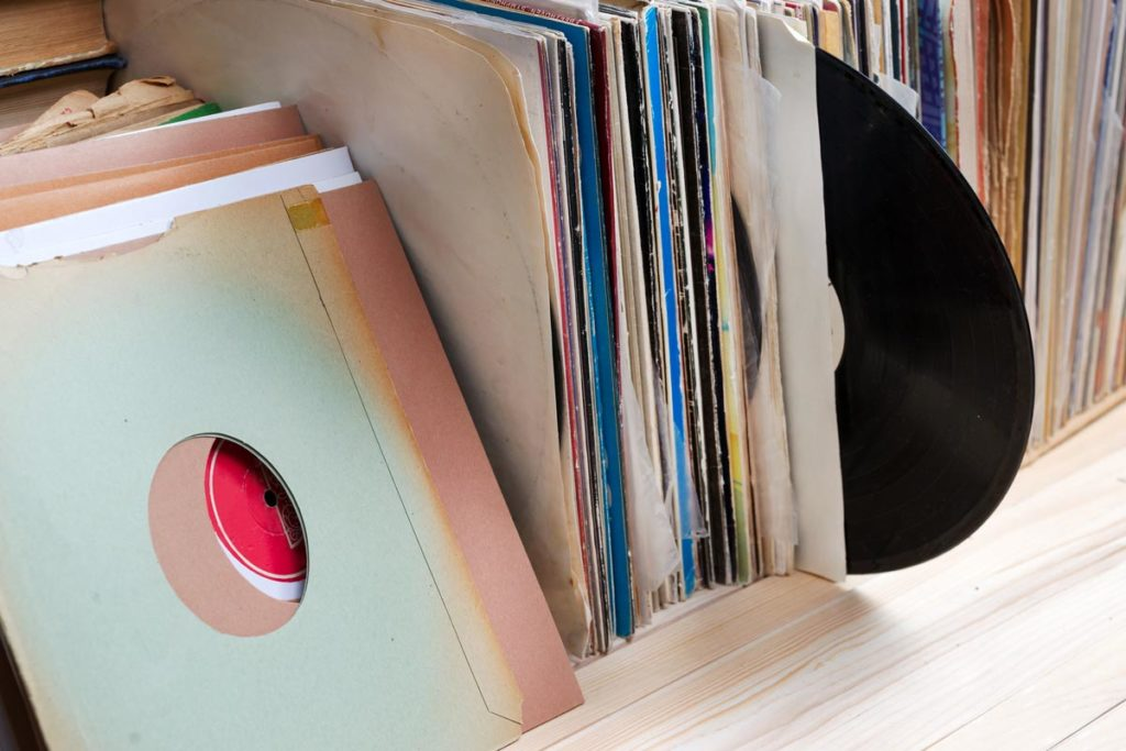 Stack of record sitting on a shelf with one sticking out