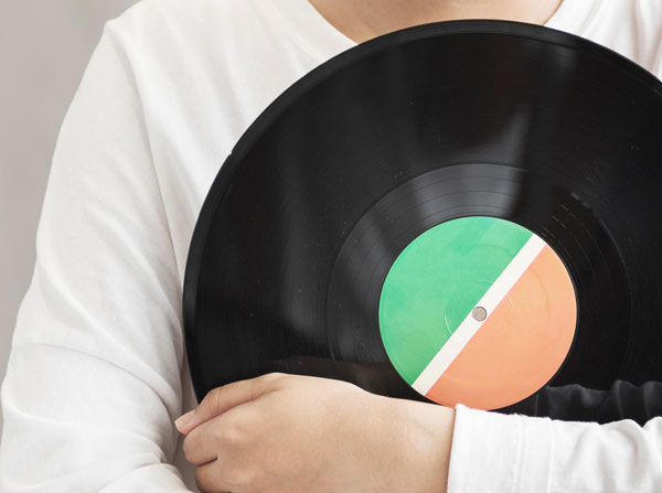Person holding vinyl record to chest