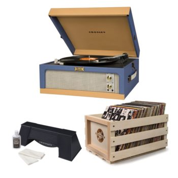 Blue Crosley Dansette record player with opened lid next to a wooden Crosley crate and a black spinning vinyl cleaner