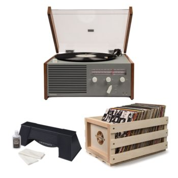 Sleek Crosley Otto with grey front and white knobs shown alongside Crosley crate full of vinyl records and plastic spinning vinyl cleaner