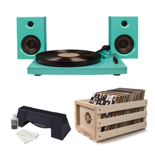 Super bright turquoise T100 turntable record player with colour matched speakers shown alongside a black record cleaner and wood crafted storage crate