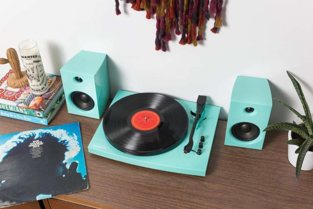 Crosley T100 turquoise turntable on a bench with guide for how to use your record player