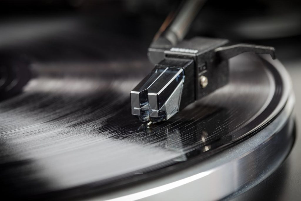 Record player arm shown with needle running along a vinyl record