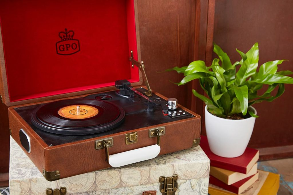 Vinyl record player shown sitting on cases