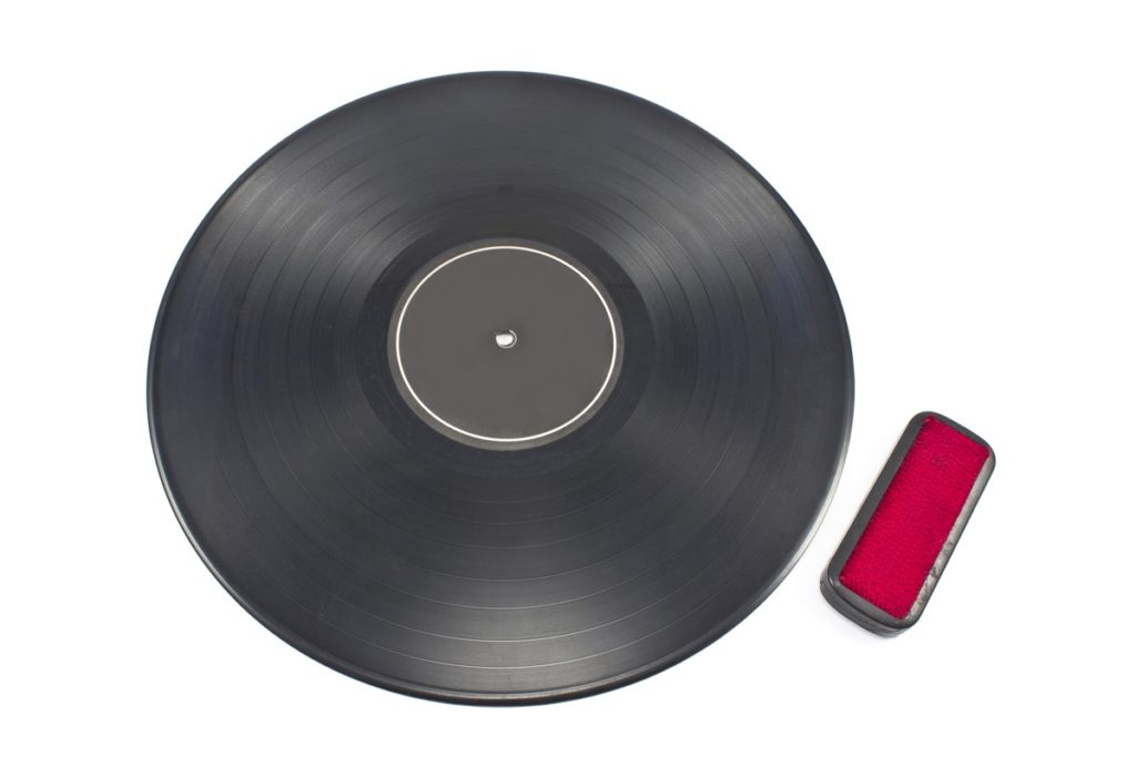 Vinyl record shown on white background with cleaning brush next to iit