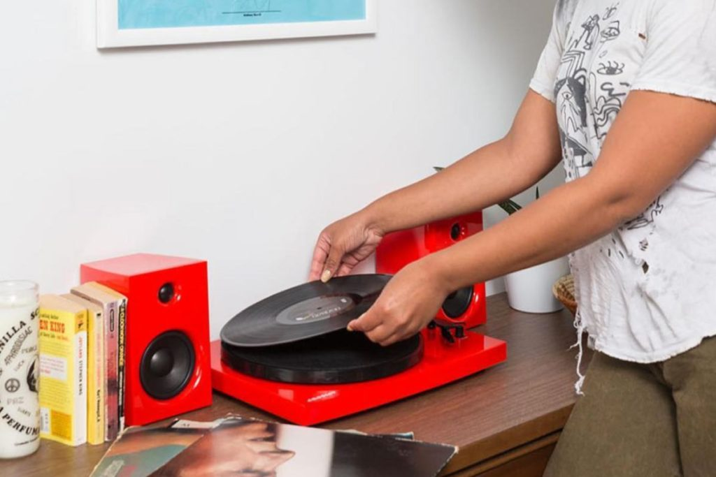 Women learning how to use a record player
