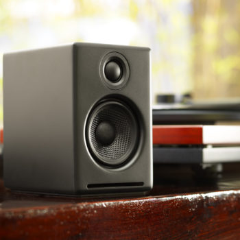 Close up lifestyle image of black Audioengine 2+ speaker in table