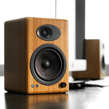 Lifestyle image of solid bamboo Audioengine 5+ powered bookshelf speakers